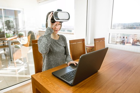 A young woman with virtual reality glasses and a laptop in an office. VR glasses, entertainment, latest technology. Stock Photo