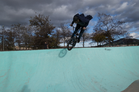 Boy riding and jumping bmx bike in a park.Extreme urban sports Фото со стока