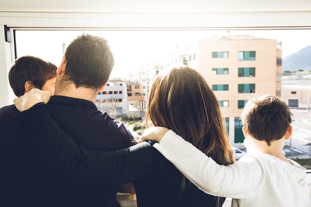 A family with kids hugging and looking out the window. Concept of a happy large family