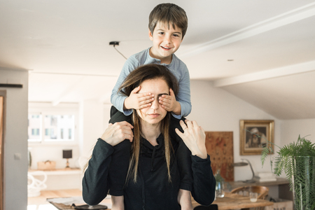 Child playing with his mother at home. Son and a mother with happy expression and smiling.Concept love between kid and mom
