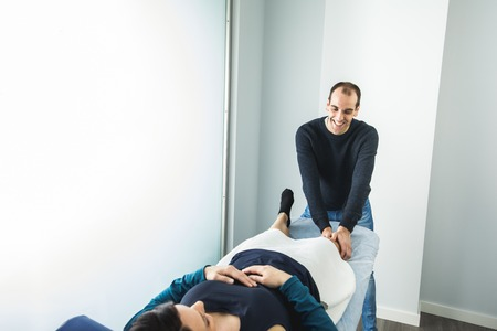 Physiotherapist treating a young woman knee. Concept of physiotherapy, rehabilitation and healing