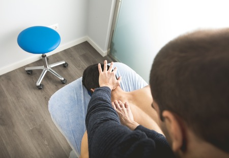 Physiotherapist massaging the back and neck of a young man. Concept of physiotherapy Zdjęcie Seryjne - 118597830