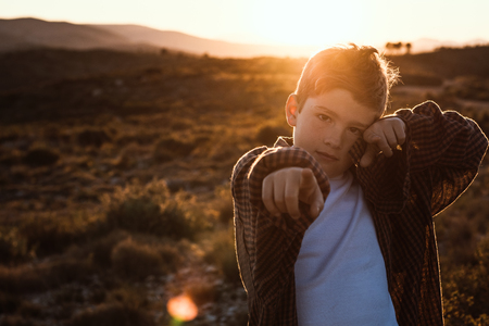 Child with fingers pointing at the camera. Child with positive expression in the countryside