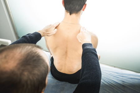 Physiotherapist examining a young man back.Physiotherapy concept and physical treatment 스톡 콘텐츠