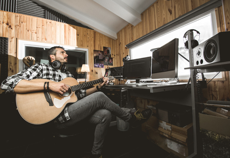 Man playing guitar in a recording studio. Concept guitarist composing songs