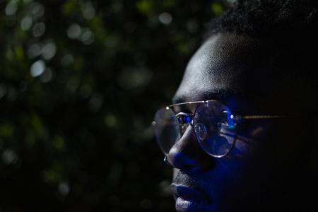Retro neon portrait of an African American. Close-up black man with modern glasses 版權商用圖片