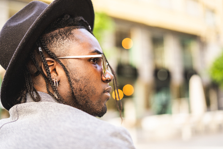 portrait of black guy with sunglasses and hat around town. African American profile Stock Photo