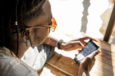 Handsome african american portrait looking at a mobile phone in a coffee shop