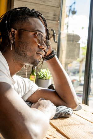 Portrait of a handsome African American guy with thoughtful expression outdoor Imagens