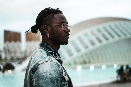 Portrait of handsome African American man on the street looking to the side with modern glasses. 스톡 콘텐츠