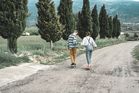 Young couple riding a skateboard on a road. Concept of millenials Skateboarders on skates
