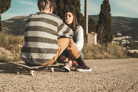 Millennial young couple happy having fun with skateboarding. Concept of young people practicing urban sports