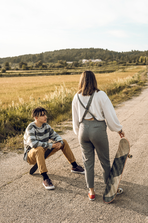 Trendy young couple having fun with a skateboard on the road. Photo style social networks
