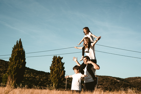 Happy and fun family in nature. Family in the countryside with arms open