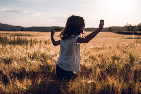 Portrait of a happy little girl running the countryside. Concept of children having fun
