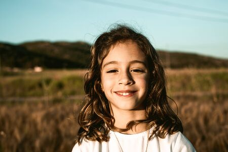 Portrait of a little girl smiling and with funny expression in the field