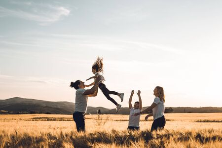 Father throws his little girl in the air. Happy family in the countryside having fun Zdjęcie Seryjne - 124997064