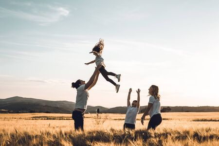 Father throws his little girl in the air. Happy family in the countryside having fun Banco de Imagens - 124997171
