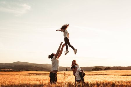 Father throws his little girl in the air. Happy family in the countryside having fun