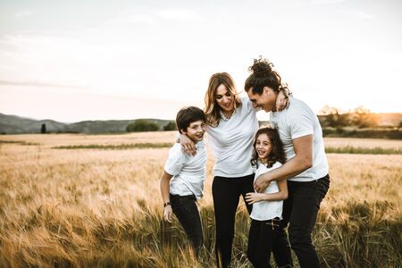 Portrait of a happy young family smiling in the countryside. Concept of family having fun in nature.