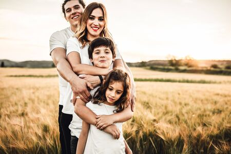 Portrait of a happy young family smiling in the countryside. Concept of family having fun in nature. Zdjęcie Seryjne - 127073246