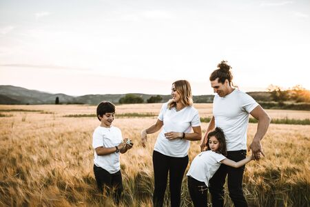 Portrait of a happy young family smiling in the countryside. Concept of family having fun in nature. Zdjęcie Seryjne - 127073247