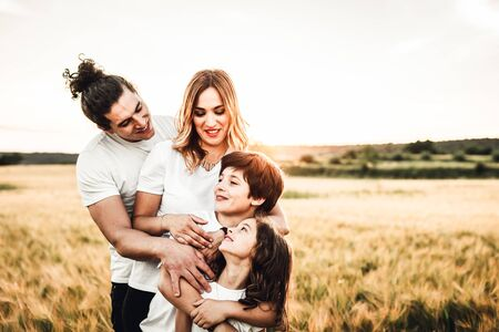 Portrait of a happy young family smiling in the countryside. Concept of family having fun in nature. Archivio Fotografico - 127073248