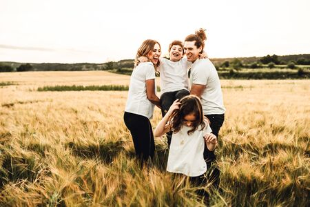 Portrait of a happy and beautiful family playing in the countryside. Concept of family having fun