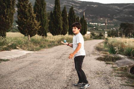 Kid playing spinning top.Concept of happy playing children