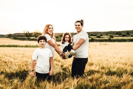 Portrait of a happy and beautiful family playing in the countryside. Concept of family having fun Zdjęcie Seryjne - 126914573