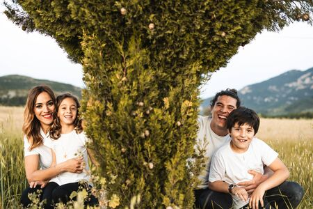 Portrait of a young family smiling and happy looking at the camera on the outside. Family having fun in the countryside Archivio Fotografico - 126916174