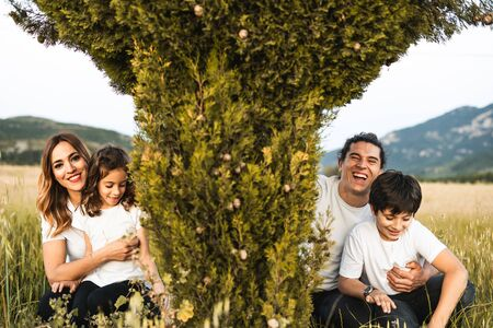 Portrait of a young family smiling and happy looking at the camera on the outside. Family having fun in the countryside