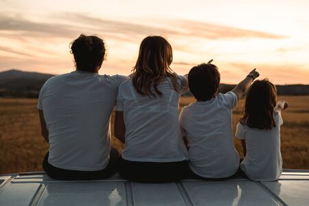 Happy family looking at the sunset in the field.Family pointing to the horizon