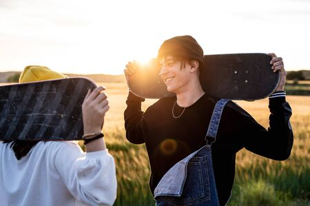Fashion Lifestyle, Happy casual young couple with skateboard, backlit at sunset