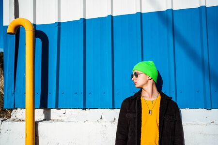 Portrait young guy in the modern city with stylish hat and blue background. Youth Lifestyle Concept