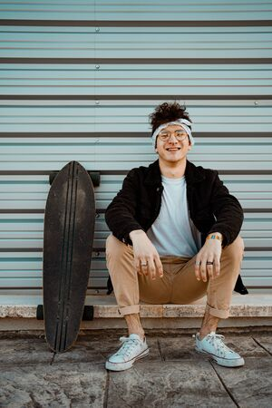Portrait guy with a skateboard. Modern skater concept
