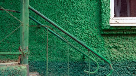 Old green wall with steel stairway