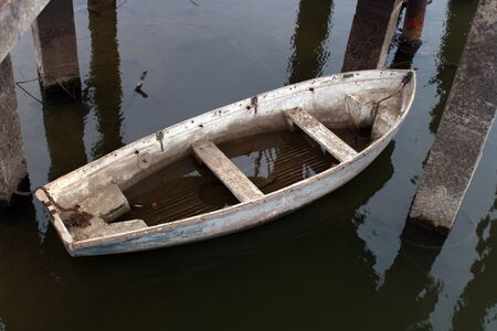 white old leaky boat half in the water on the river 스톡 콘텐츠