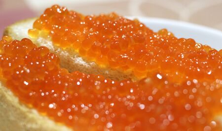 red fish caviar on bread. enjoy your meal.