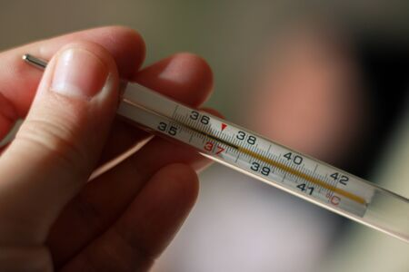 An alcohol thermometer shows a temperature of 37.9 on a blurred background of a sick girl lying on a bed. Check the temperature. Fever, illness, chills, care.
