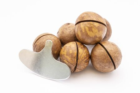Fruits of the Australian macadamia nut and iron key on a white background. Kernels with a Shelled Shell
