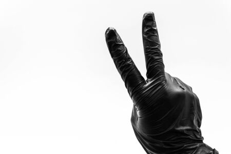 Female hand turned back to front in black gloves show gestures, signs and symbols isolated on white background. Two fingers to the top and folded in the form of V signifying victory or peace hi.  Stock Photo