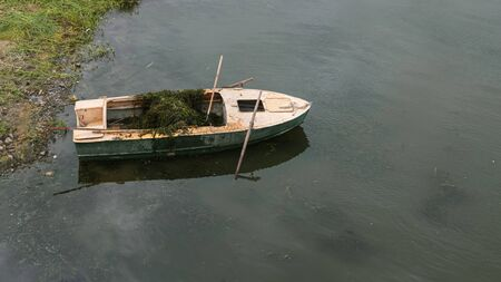 Old boat in the lake near the shore. Water purification of the river from algae.