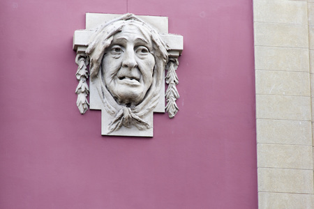 sculp: countenance visage phiz mug frontispiece feature muz face appearence wall sculpture carving sculp pink wall stone old lady