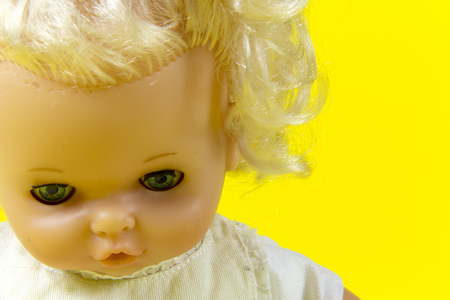 dolly: vintage doll, dolly, puppet, old toy, retro, yellow background, blue eyes, blond hair, infant, infantile, childish Stock Photo