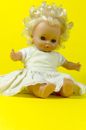 infantile: vintage doll, dolly, puppet, old toy, retro, yellow background, blue eyes, blond hair, infant, infantile, childish Stock Photo
