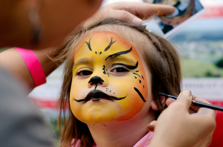 female face closeup: Cute little girl with face painted like a lion.
