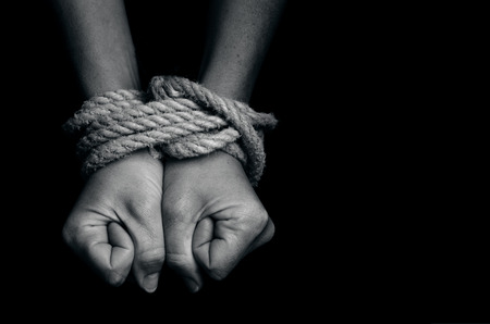 Hands of a missing kidnapped, abused, hostage, victim woman  tied up with rope in emotional stress and pain, afraid, restricted, trapped, call for help, struggle, terrified, locked in a cage cell. 스톡 콘텐츠