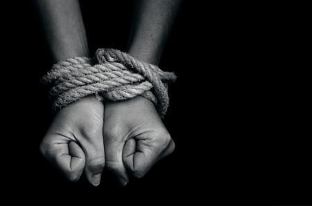 Hände eines fehlenden entführt, missbraucht, Geisel, Opfer Frau mit einem Seil in emotionaler Stress und Schmerz, Angst, eingeschränkt, gefangen gefesselt, rufen um Hilfe, Kampf, erschrocken, in einem Käfig Zelle gesperrt.