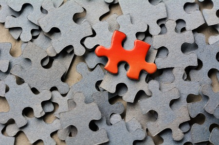 the difference: Orange puzzle pice standing out from larger group puzzle pieces. Business concept - branding, different, original. Stock Photo